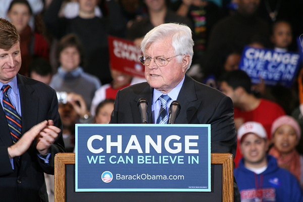 "Senator Ted Kennedy speaks into microphone at podium adorned with sign reading ""Change we can believe in"" endorsing then-Senator Barack Obama for President."