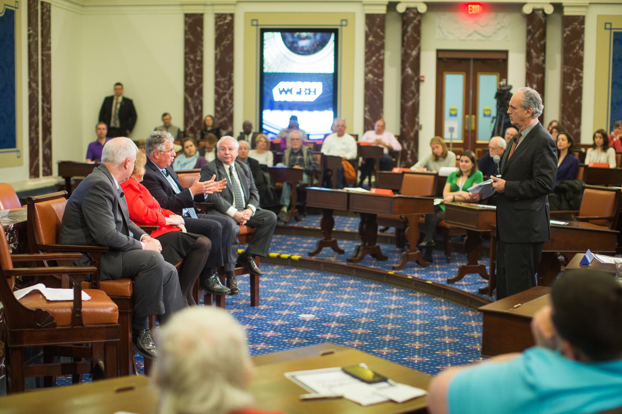 Eric Haynes hosting a panel discussion at the EMK Institute's Senate Chamber