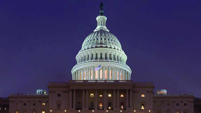 An American flag flies in front of the Capitol Dome at night